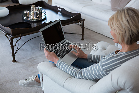mulher usando laptop na sala