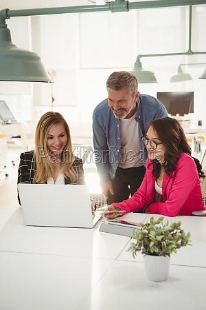 executivos discutindo sobre laptop na mesa