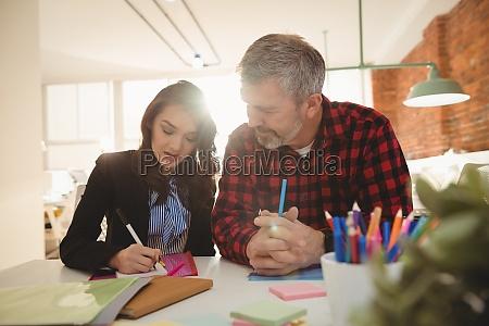 executivos de negocios escrevendo em notas
