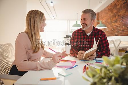 executivos sorridentes discutindo sobre o diario
