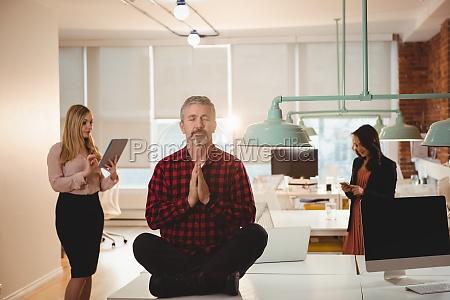 executivo masculino meditando sobre mesa no