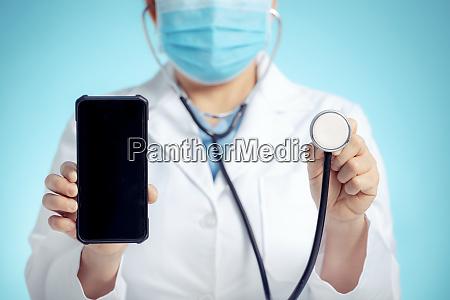 medico com estetoscopio e telefone inteligente