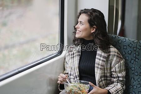 mulher jovem sorridente almocando em um