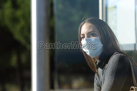 mulher usando uma mascara esperando em