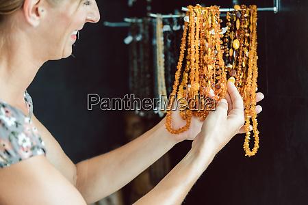 mulher olhando para um colar feito
