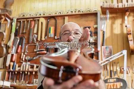 violinista verificando instrumento acabado para sua