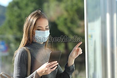 passageiro com mascara protetora verificando horario