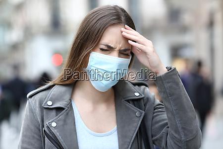 mulher com mascara protetora sofrendo dor