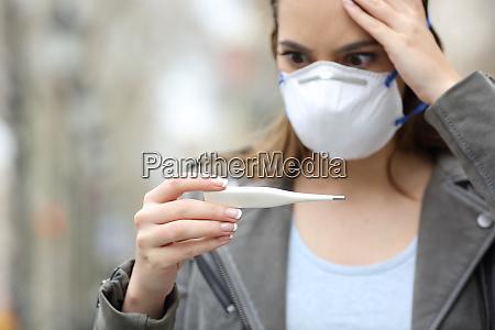 garota preocupada com termometro de verificacao