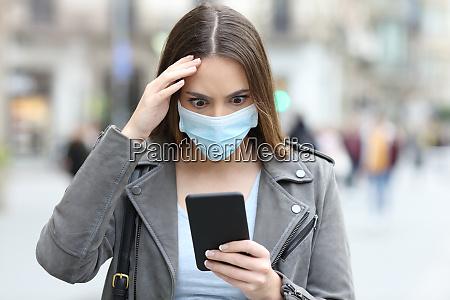 mulher preocupada com mascara verificando telefone