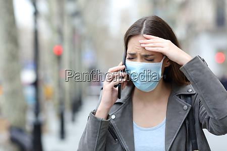 mulher preocupada com mascara protetora chamando