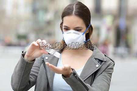 menina com mascara aplicando desinfetante para