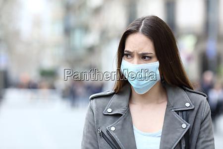 mulher assustada com mascara protetora evitando