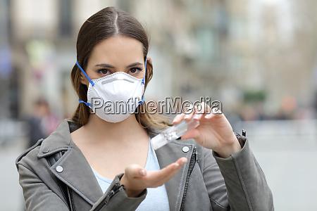 mulher com mascara protetora usando desinfetante