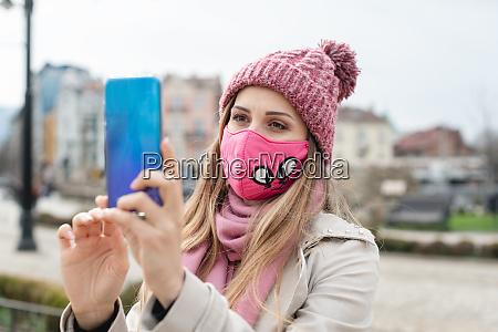 mulher usando mascara de corona fazendo