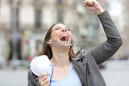 mulher animada celebrando segurando mascara na