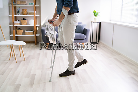 disabled man using crutches to walk