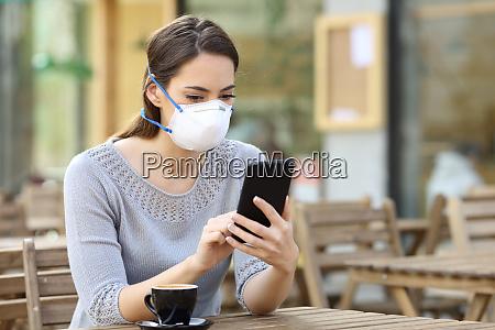 mulher com mascara verificando noticias no