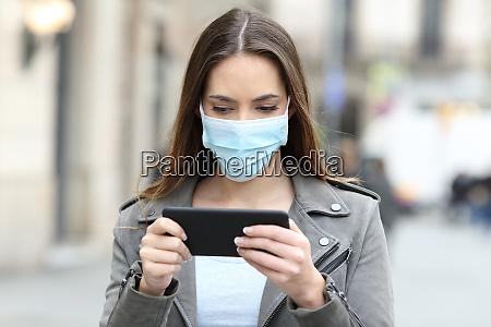 mulher com mascara assistindo video no