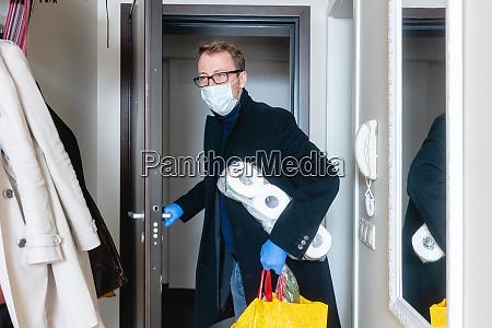 homem usando mascara medica voltando para