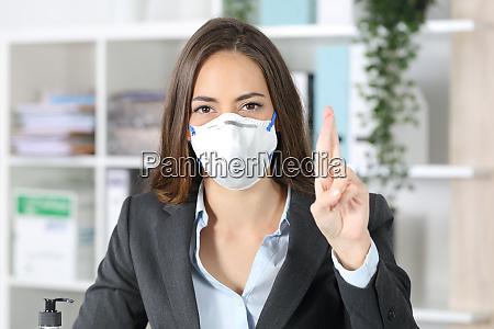 executivo com mascara cruzando dedos olhando