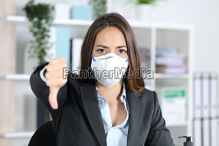 executivo com mascara gesticulando polegares para