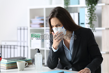 executive wearing mask coughing and sneezing
