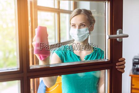 mulher limpando janelas durante o bloqueio
