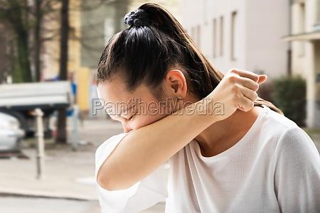 flu sick woman sneezing in elbow