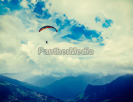 paraplane in sky above mountains