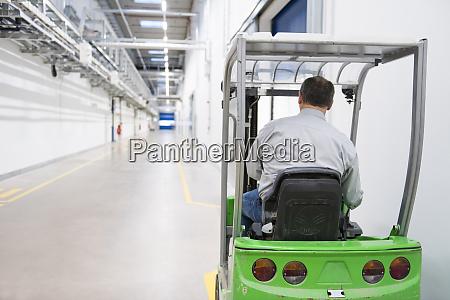 homem em empilhadeira em uma fabrica