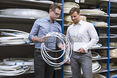two, businessmen, examining, a, product, in - 28745213