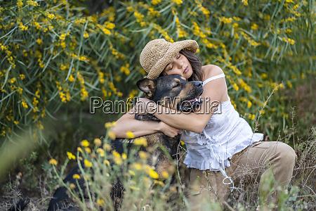 jovem usando chapeu enquanto abracava cachorro