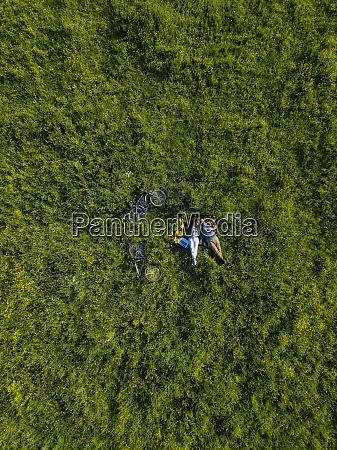casal deitado na grama vista aerea