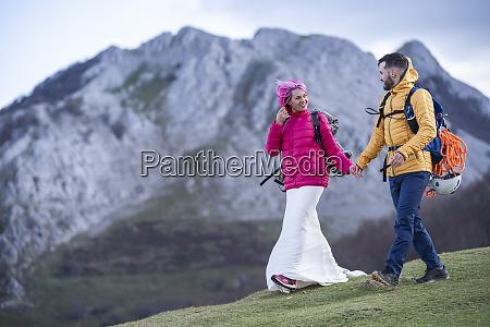 casal de noivas caminhando com mochilas