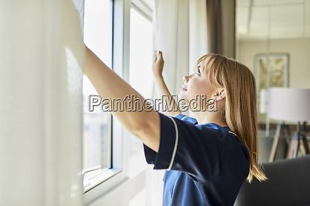 camareira sorridente abrindo cortinas de janela