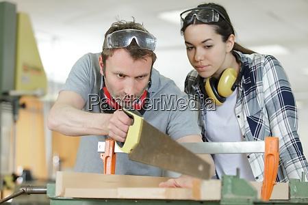 carpinteiro e aprendiz trabalhando juntos em