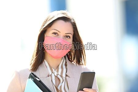 empresario com mascara e telefone posando