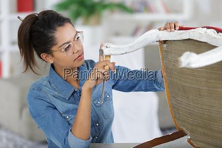 uma mulher fixando uma cadeira