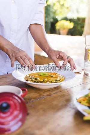 mulher enfeitando comida para o almoco