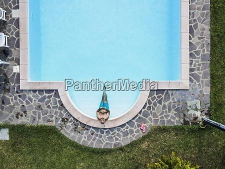 vista drone do homem relaxando piscina