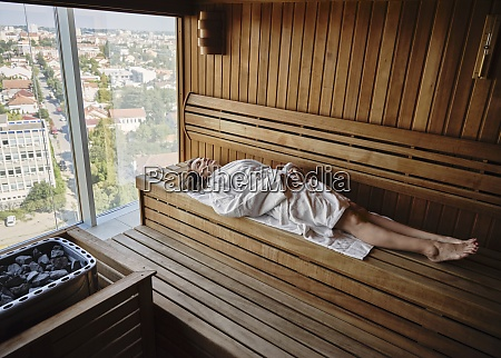 idosa relaxando em sauna de madeira