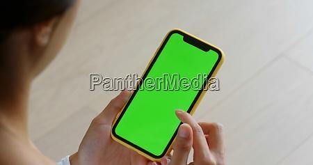mulher usa celular com tela verde